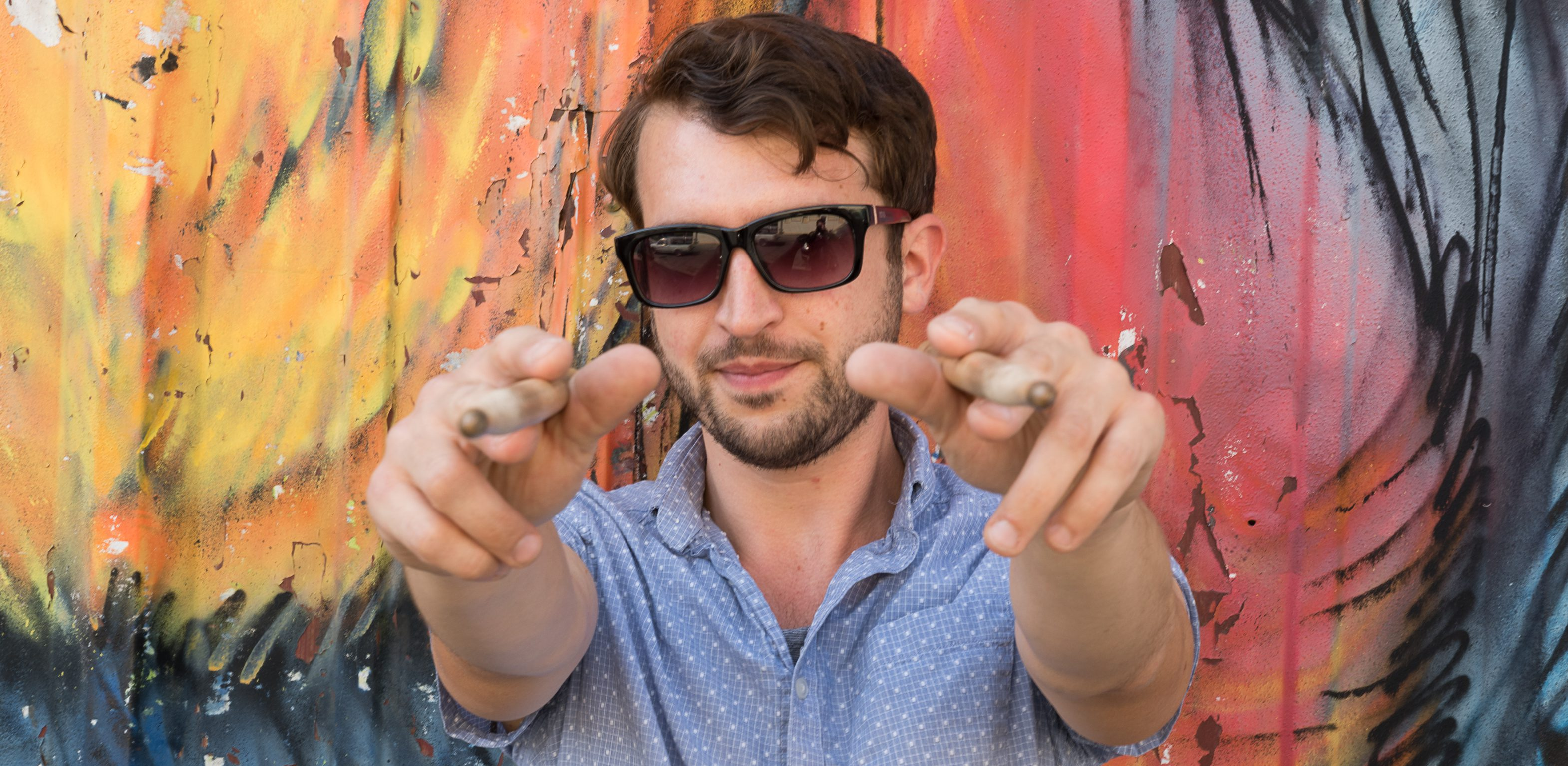 Adam Everett with drum sticks in front of a colorful wall